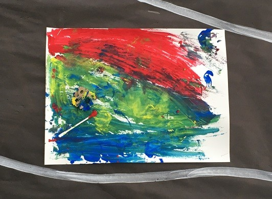Abstract painting on a wall display with blue, red, and green paint and a cotton swab and cardboard stamp attached.