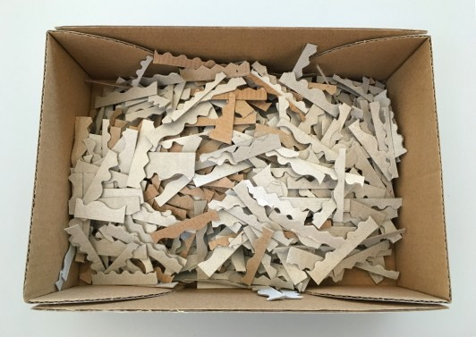 A box filled with small cardboard pieces with shaped edges.