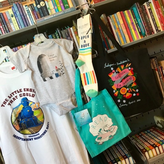 Two t-shirts, a pair of socks, and two tote bags are hung up along the front of a shelf full of books in The Carle Bookshop.