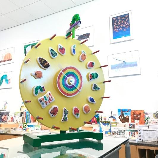 A large yellow and green prize wheel sits on top of a glass table in The Carle Bookshop with images from The Very Hungry caterpillar on each notch.