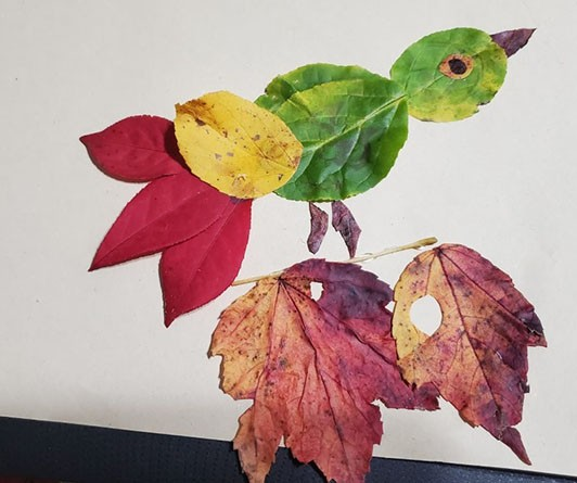 Collage of a bird perched on a branch. The bird is made of bright red, yellow, and green leaves.