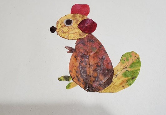 Collage of a chipmunk made from a variety of red, yellow, and brown leaves.