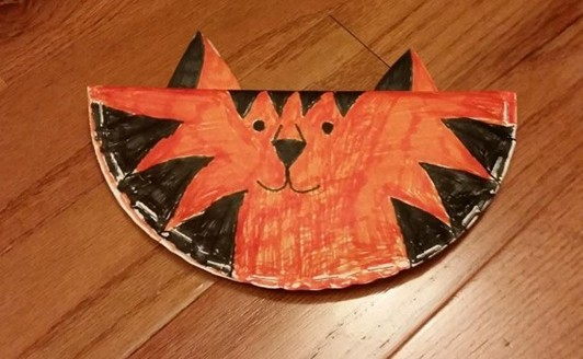 paper plate folded in half and stapled with a tiger face drawn on with markers