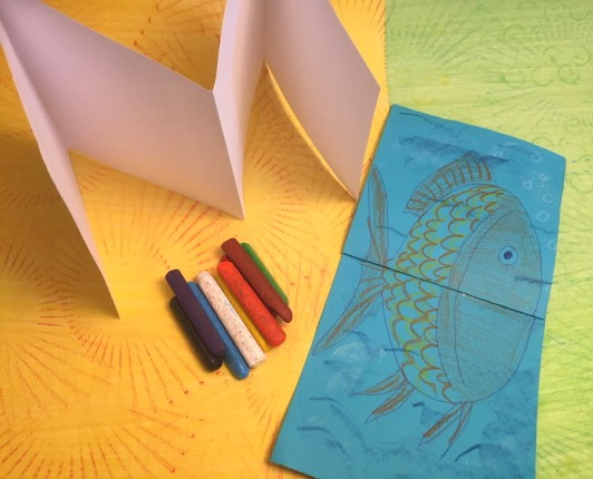 An accordion-fold book with a fish drawn on it next to some crayons and an empty accordion-fold book, all on top of colorful textured papers.