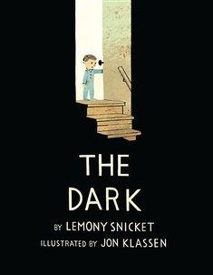 A child in pajamas opens a door and sheds light down a dark stairwell.
