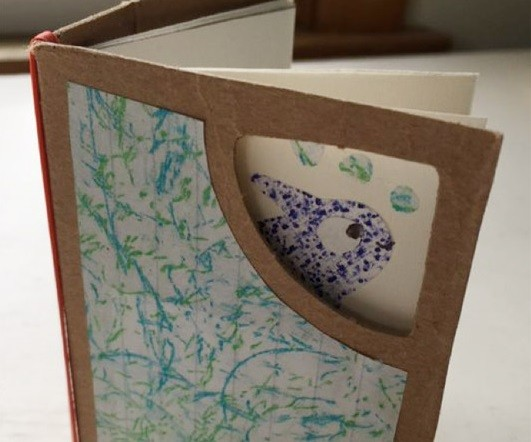 Book with cardboard cover that has a window cut out in the corner so you can see part of a fish on the first page of the bok.