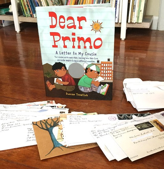 Picture book Dear Primo in front of bookshelf with display of handwritten letters in front. Cover shows two boys, back to back, writing each other letters.