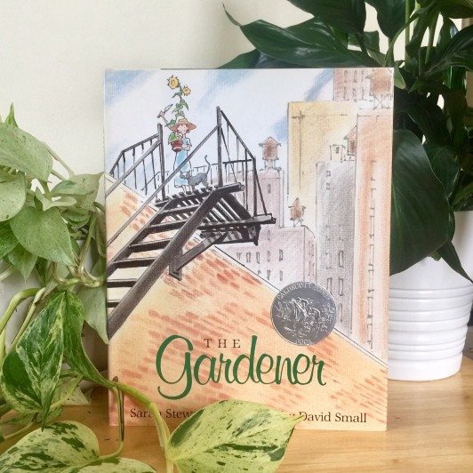 Newbery honor picture book The Gardener by David Small and Sarah Stewart propped in front of plants
