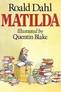 Cover of Matilda girl sits on box with a book open in her hands and many books surrounding.