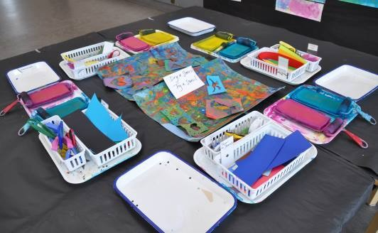 Art studio table with stamp pads, brayers, cutting tools, and scarp papers organized in trays and baskets