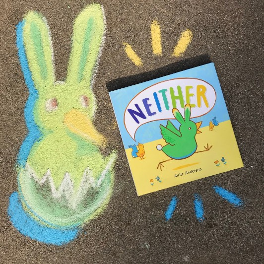 The book Neither by Airlie Anderson lies on a gray cement sidewalk next to a chalk drawing of its main character.