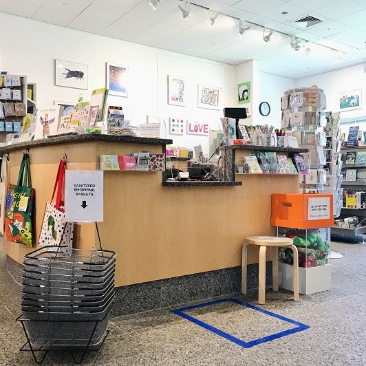 The register in the Bookshop with plexiglass divider, sanitized baskets, and social distancing tape on the floor.