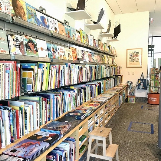 The picture book wall at the Carle Bookshop with blue tape on the floor to help visitors stay six feet apart.