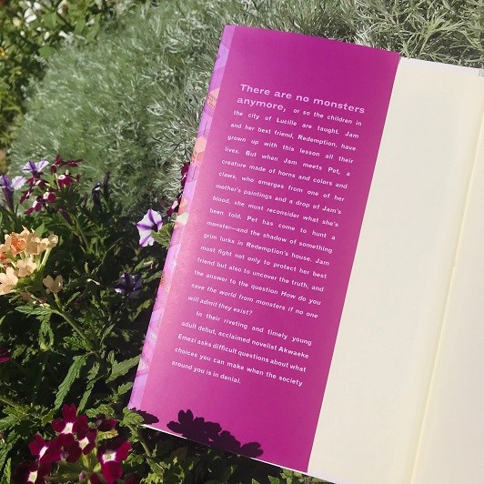The novel Pet by Akwaeke Emezi sits open in a garden of flowers and green brush to show its summary on the dust jacket.