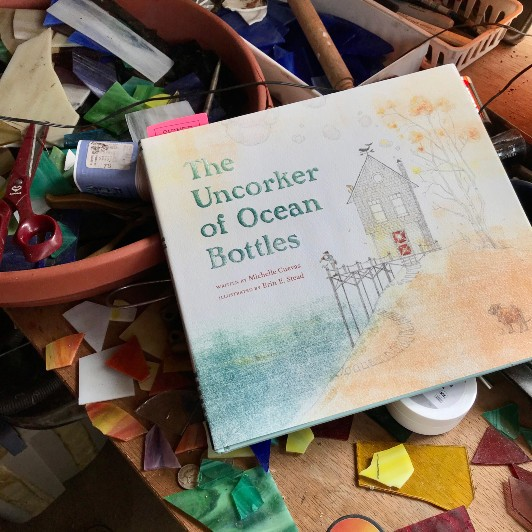 The book The Uncorker of Ocean Bottles placed on top of stained glass art project materials