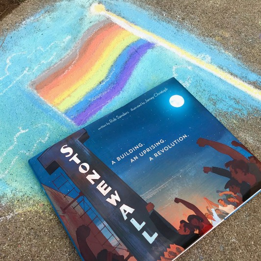 The book Stonewall lays on a chalk drawing  of the Philadelphia Pride flag with stripes of brown and black at the top representing black and brown queer people.