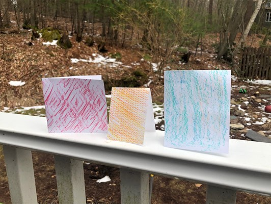 Textured papers folded into cards and sitting on a railing.