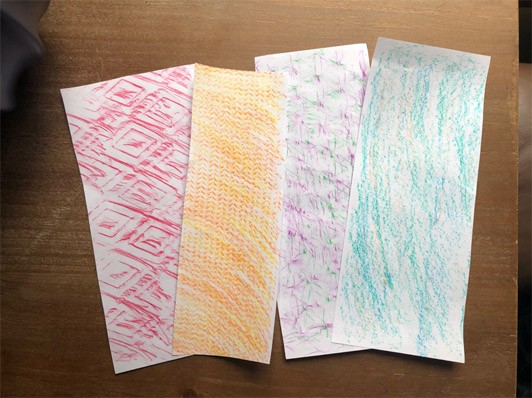Four papers with different texture rubbings including red diamonds and orange chevrons.