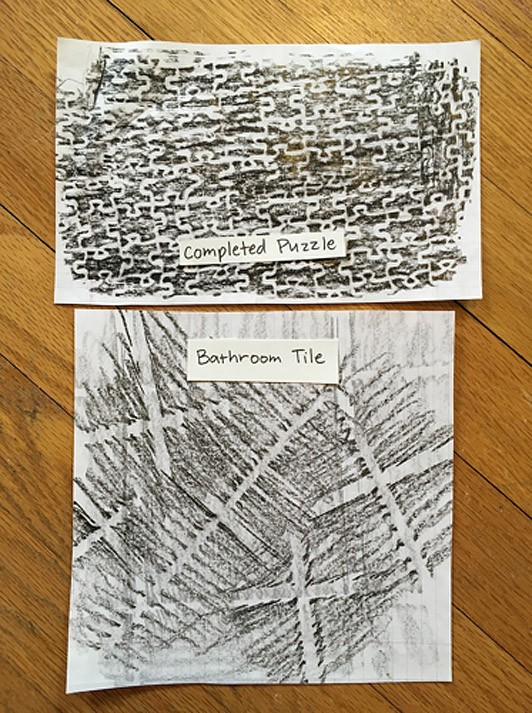 Black and grey texture rubbings of a completed puzzle and bathroom tile.