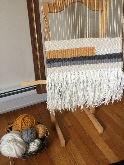small standing loom with progress shot of white and gold weaving