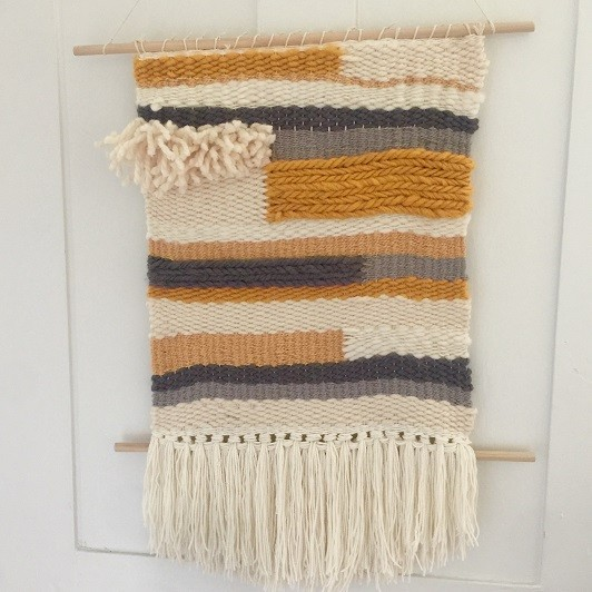 wall hanging of white, grey and gold fibers