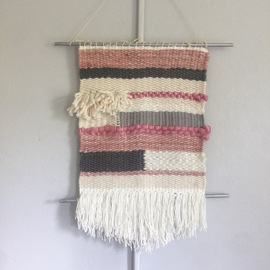white, grey and pink wall hanging of warn fibers with tassels