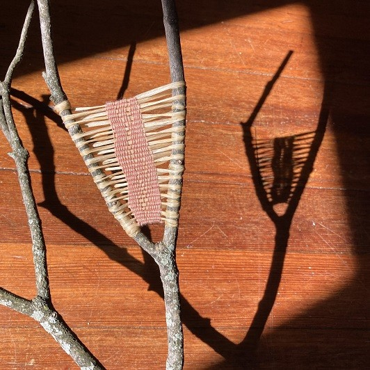 weaving on forked tree branch held in sunlight to show shadow pattern