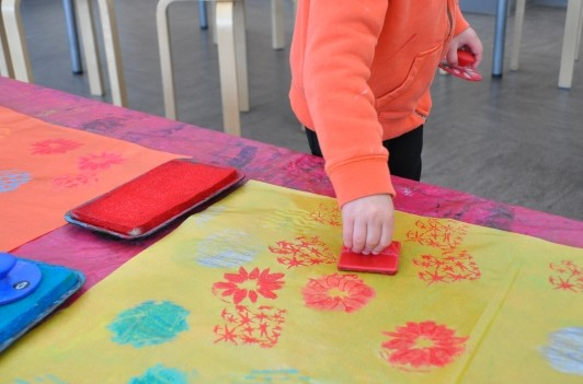 Hand of a child stamping with red onto yellow paper.