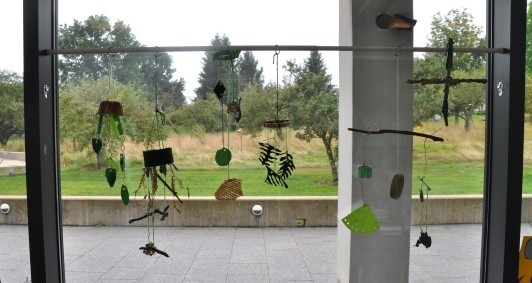 Window display with 6 plant-inspired mobiles hanging