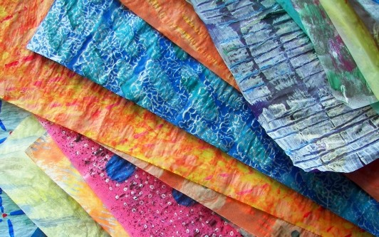 Stack of painted papers with various textures, colors, and patterns.
