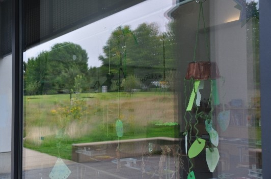 A plant mobile in the window with a reflection of Bobbie?s Meadow on the left.